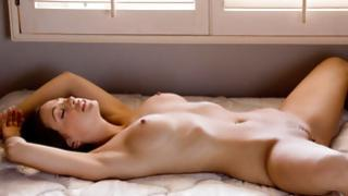 College coed lying on the ottoman thoroughly undressed performing her flexible pale skin